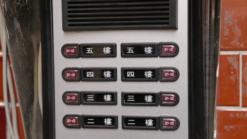 An apartment door buzzer with multiple rows and intercom with Mandarin Chinese numbers and a hand pushing the floor
