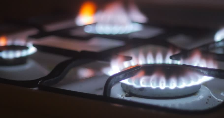 Dark Kitchen At Night gas burner stove for cooking, yellow and blue flames, burning gas