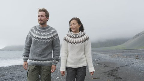 Iceland couple wearing Icelandic sweaters on black sand beach. Woman and man model in typical Icelandic sweater looking at ocean enjoying view of nature landscape at ocean sea. 60 FPS RED EPIC.