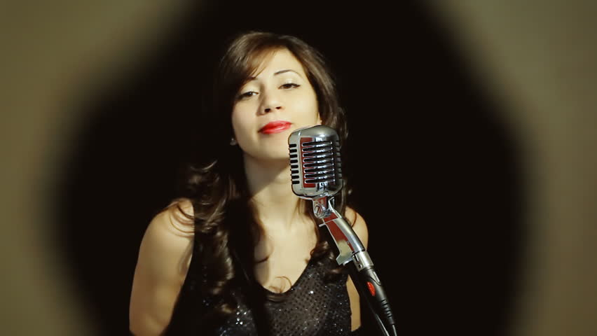 A classy young woman singing on stage with a retro vintage microphone (called Elvis or Fatty), seen through a warm antique frame, dancing. Medium shot, black background.