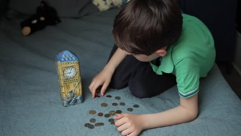 Boy counting coins, child puts money in a piggy bank, kid saving money