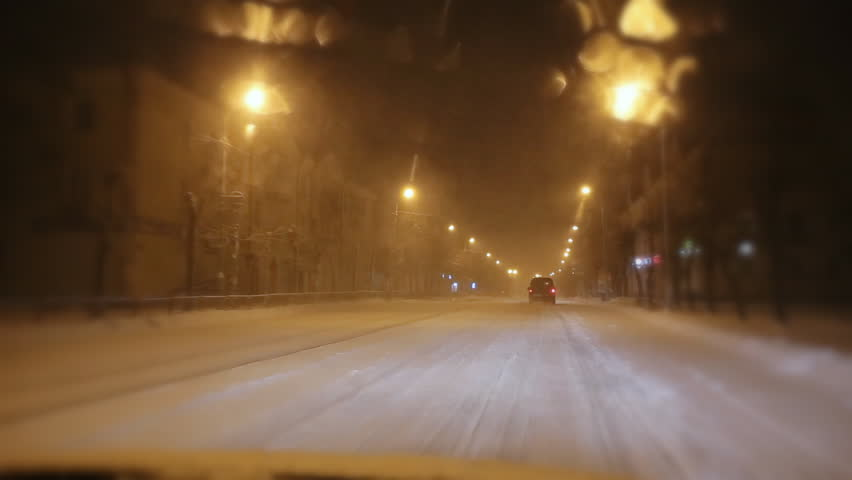 Snow-covered winter road from the windshield of the car at night in the light of the lamps and automobile headlights. Blizzard and heavy snowfall. Christmas and New Year weather