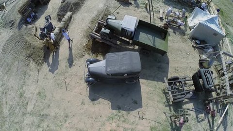 NELIDOVO - JUL 12, 2014: People in military uniform get rest at camp during reconstruction Battlefield at summer day. Aerial view