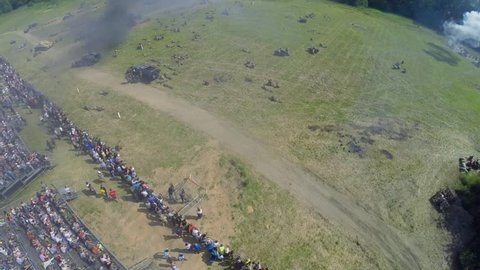 NELIDOVO - JUL 12, 2014: People watch fight of Soviet and German armies during reconstruction Battlefield at summer day. Aerial view