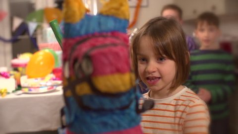 Little girl hitting a pinata at party while his friends cheer him up in slow motion