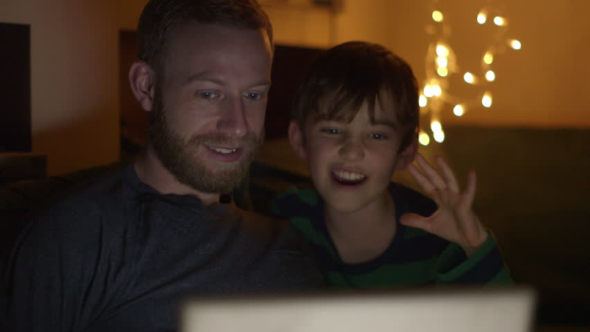 Father and son enjoying a movie on tablet