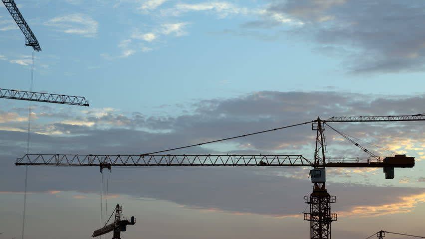Construction cranes fading in the night, time-lapse