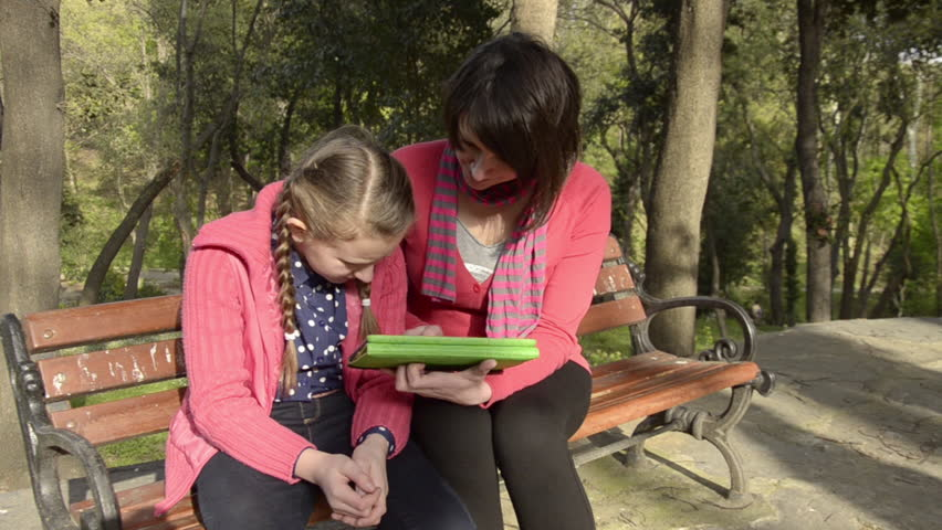 Little, blonde, red, pink cardigan, sweater  girl show pictures to her beautiful, mom on a tablet computer at a public park, garden. | Shutterstock HD Video #8671075