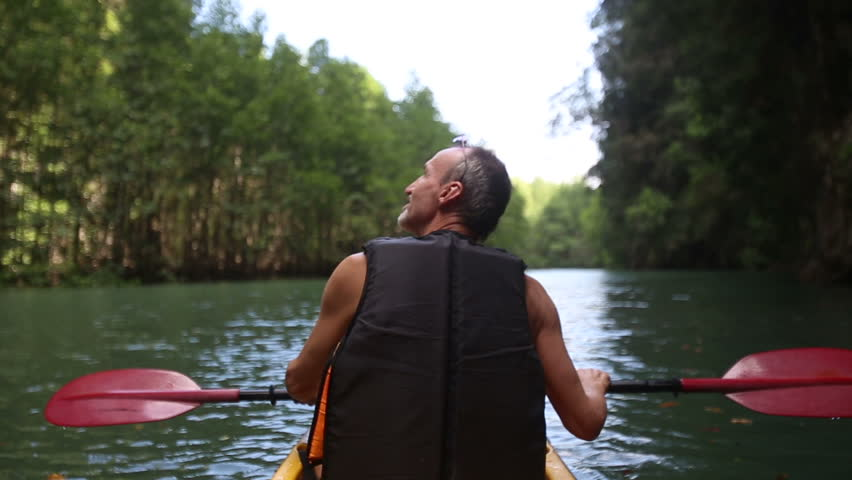 elderly man swim down the river on kayak looks around and points by his finger