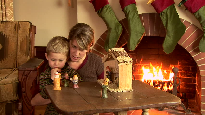 Mother and son with nativity scene at Christmas