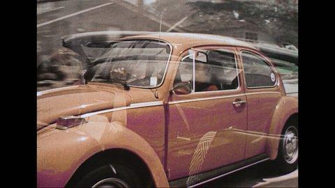 UNITED STATES - CIRCA 1970s: A convertible peels away through a dirt path. A woman drives an orange VW Beetle. A young woman drives a convertible. A brown, covered convertible drives down a street.