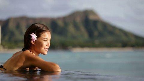 Hawaii vacation wellness pool spa woman relaxing in warm water at luxury hotel resort. Young adult at Waikiki beach in Honolulu, Oahu, Hawaii, USA.