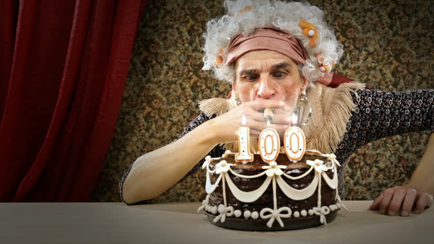 Funny senior woman is celebrating her birtHDay lighting up a cigar from a candle - HD video footage