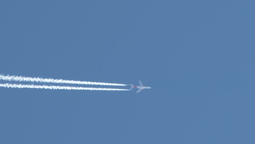 4K - Airplane flies overhead through frame on clear, blue sky day leaving behind vapor trail jet contrails.