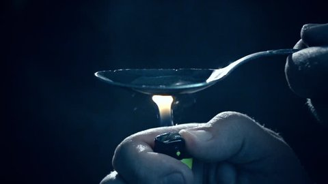 Man's hand sets fire the lighter over spoon of boiling drug, diluted heroin. Slow Motion. Social degradation, self-destruction of narcomaniac junkie.