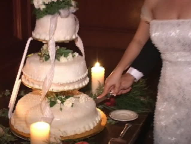 bride and groom are cutting wedding cake