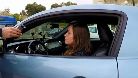 young beautiful woman driver undertaking clinical test for alcohol content state using a breathalyzer