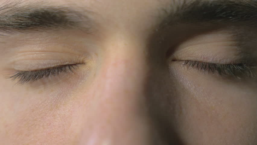 4k UHD - Close-up of a young man eyes opening and blinking