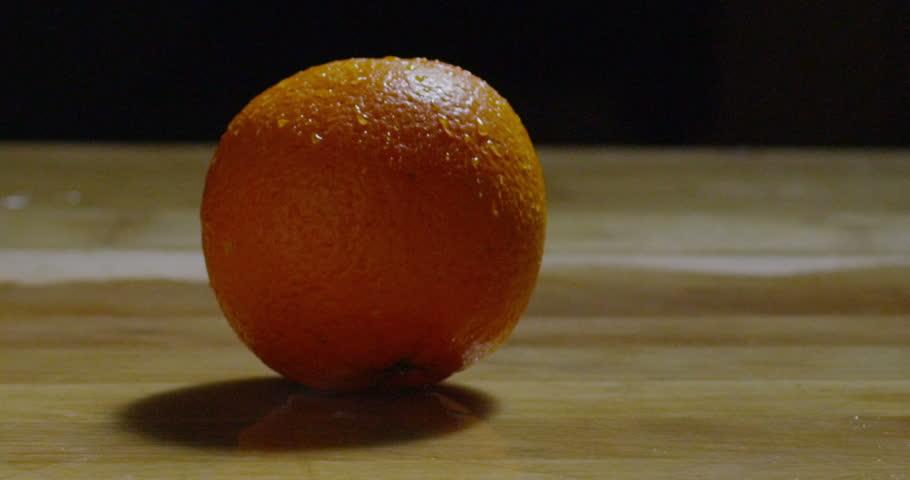 super slow motion macro of a single amber orange fruit (extra