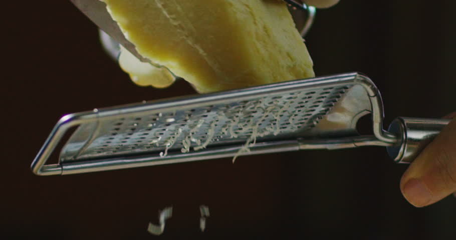 Super slow motion macro of a middle aged chef grating parmigiano-reggiano cheese with steel grater on the dish (close up)