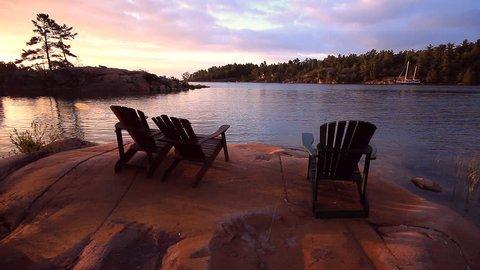 Scenic setting of Ontario cottage country, with three Muskoka Chairs aka Adirondack Chairs, at sunrise