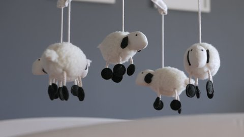 Lamb Nursery Mobile spinning above Baby Crib, Medium shot with picture frames in background.