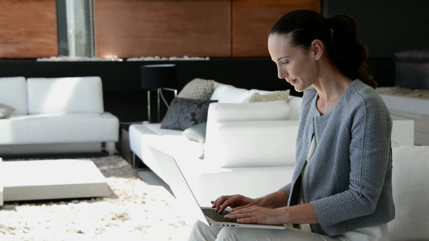 Woman sitting in a beautiful living room, using a laptop. | Shutterstock HD Video #8873245