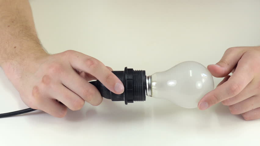 Man's hands are testing light bulb socket on white table
