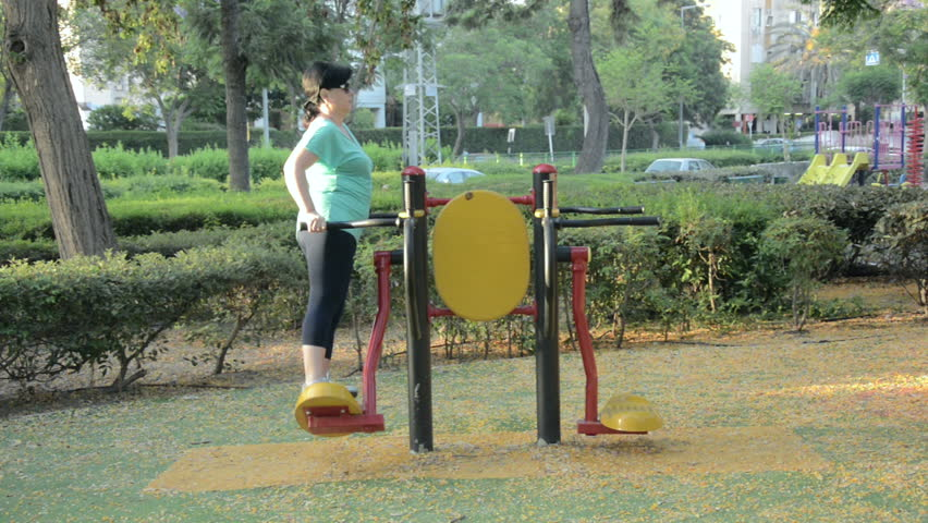 50 year old woman is enhancing body coordination and flexibility on surfboard station outdoor early in the morning