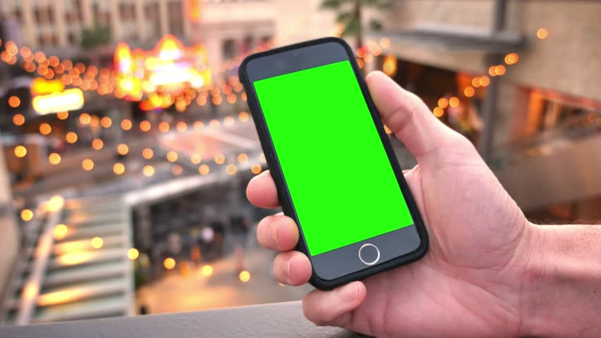 A man uses a green screen smart phone on the streets of Hollywood.  With optional luma matte.