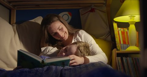 7 year old boy and his mum having a loving moment when reading a bedtime story