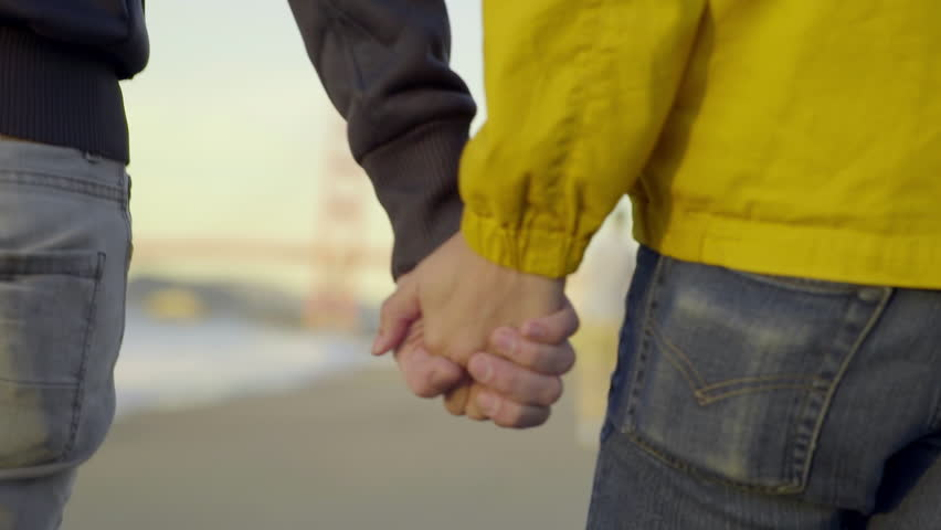 Gay Couple Hold Hands And Walk Down Beach Toward Golden Gate Bridge (Slow Motion)