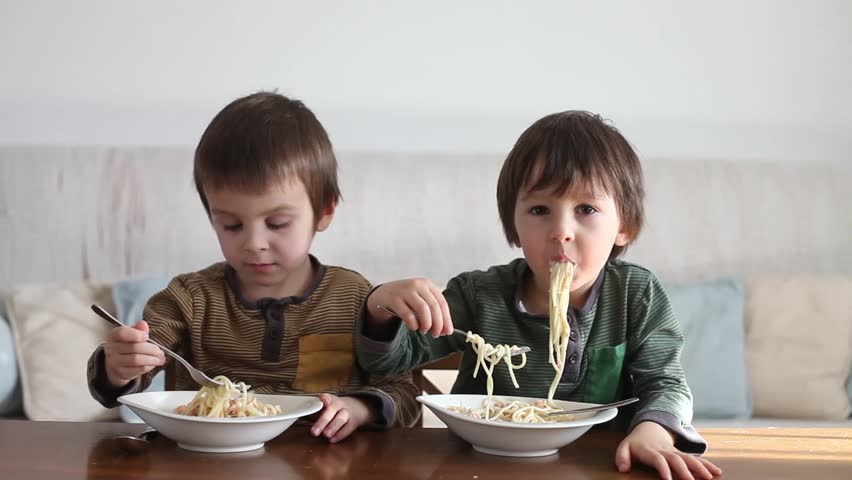 Adorable little kids, eating spaghetti at home, homemade pasta