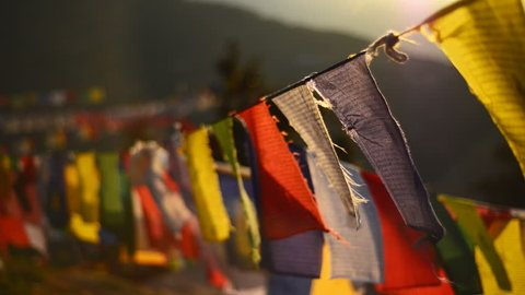 Buddhist prayer flags swaying in the wind. Shallow depth of field.