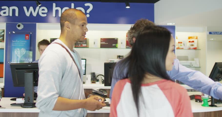 4K Helpful salesman serving customers in consumer electronics store showroom