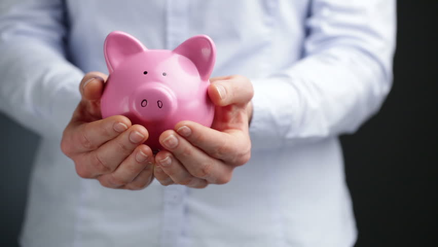 A young businesswoman holds a pink piggy bank at waist level with copy space on the side. | Shutterstock HD Video #8946535