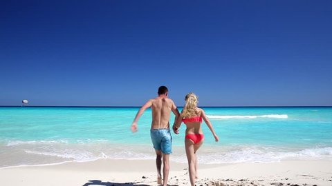 Young couple running in to the ocean on caribbean beach, Cancun, Mexico