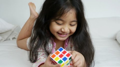 PHITSANULOK, THAILAND - FEBRUARY 10 : Little Asian girl playing with rubik's cube on the bed on February 10, 2015 in Phitsanulok, Thailand