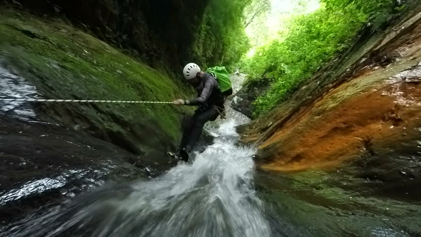 Canyoning Instructor Rappelling Close To Impressive Waterfall , Includes Audio , Model Released Footage