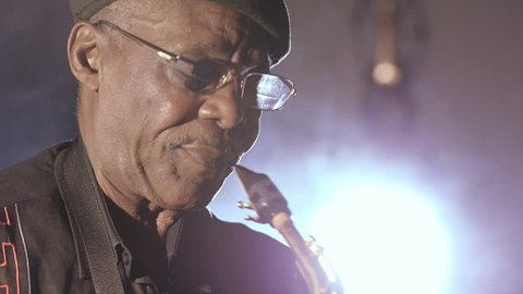 Old African American man playing saxophone on dark background, closeup