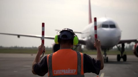 Airport ramp agent worker supervisor  shows direction by two striped sticks for parking to the aircraft that landed and moving to terminal for disembarkation of flown passengers  on Airbus A319 A320