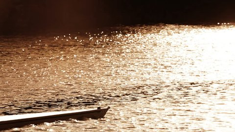 Oarsmen in training on the water at sunrise, seen in silhouette
