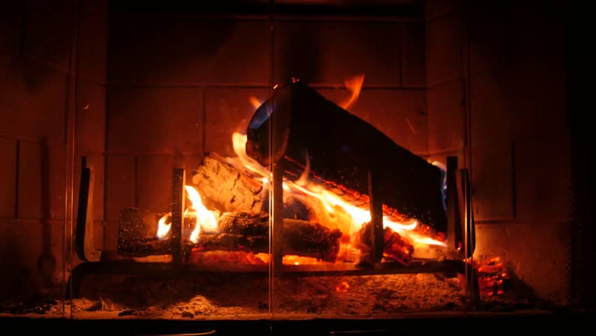 A dolly shot of a hot fire in a living room fireplace in the house - - A Roaring Fire Blazing Away In An Old Fashioned Fireplace Stock