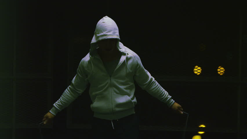 4K Slow motion hooded male athlete skipping at night with a jump rope in urban setting, shot on RED EPIC #9072005
