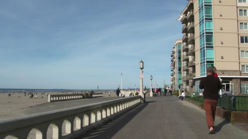 People walking on boardwalk in Seaside, Oregon on beautiful sunny day.
