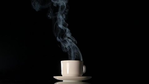 White cup with very much hot smoking black coffee on dark background