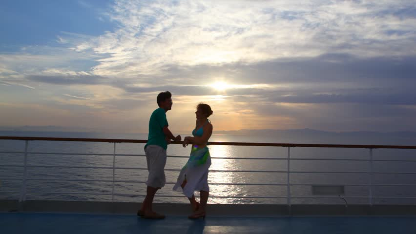couple having joined hands stands on ship moving in sea during sunset