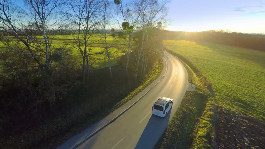 Aerial of vehicle driving towards the sunset 4K. Aerial jaw shot around a white family car with panoramic glass roof driving on green countryside road.