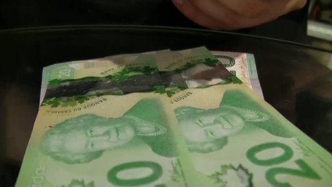 TORONTO - CANADA MARCH 1 2015 Counting Money bunch of 20 Canadian dollars bills with picture of Queen Elizabeth close up