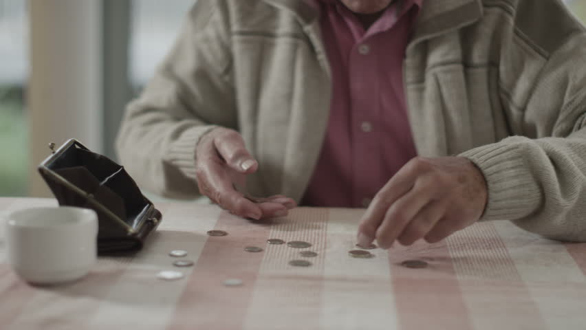 4K Confused senior man trying to count out coins from a purse